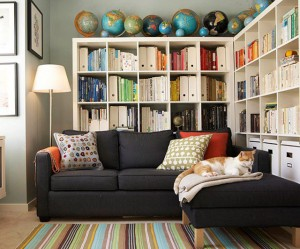 A collection of globes along the top of the bookshelves creates a unique display