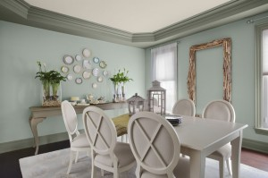 A white dining room set against pale green walls stands out