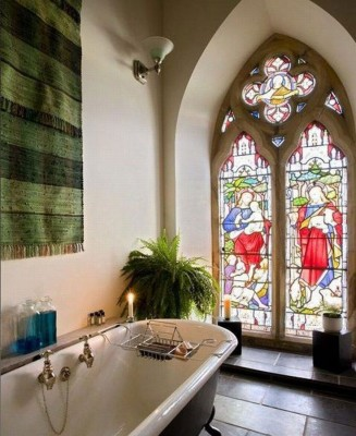 A beautiful stained glass window highlights the bathroom in this church to home conversion