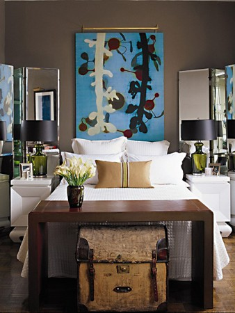 A large painting brings color and interest to the bed wall