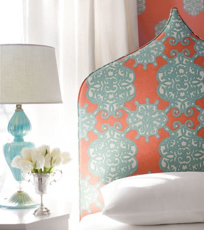 A pretty palette of aqua and coral mix on this upholstered headboard, accented with an aqua lamp