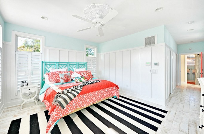 A bold black and white striped floor contrasts boldly with the aqua and coral bedding