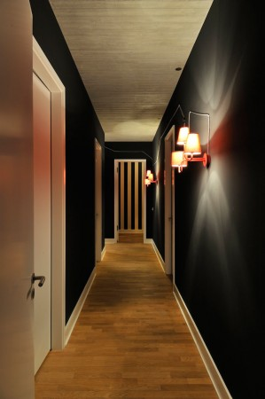 Sconces illuminate a stylish dark hallway