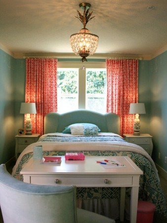 Coral drapes and accents highlight this aqua painted bedroom