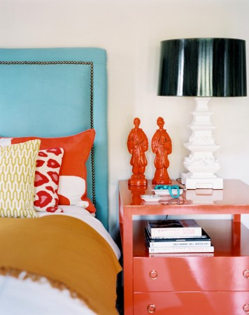 Coral accents stand out against an aqua headboard