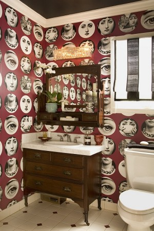 A color variety of Fornasetti wallpaper is an appealing and unique powder room accent