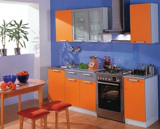 Blue walls make the orange cabinets pop in this kitchen