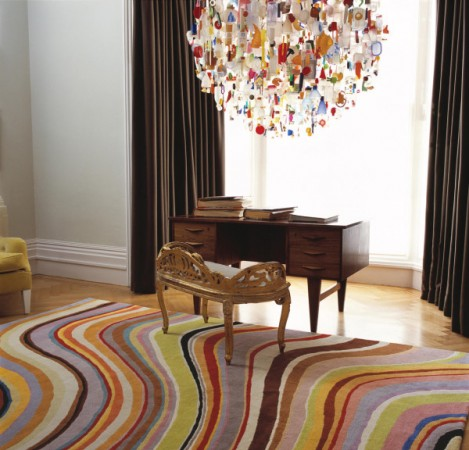 Flowing color in the rug is mimicked in the chandelier