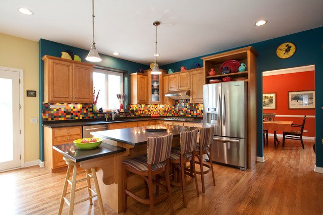 Dark teal walls and colorful backsplash tiles wake up this kitchen