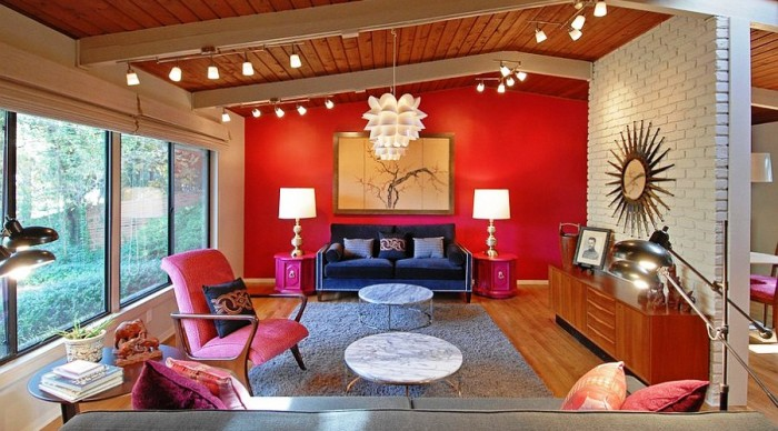 A vibrant red accent wall and a mix of blue and fuchsia create a welcoming space