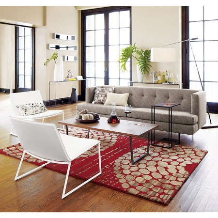 Red area rug provides a burst of color and contrast for this room