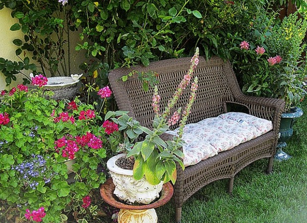 A wicker bench makes a perfect garden getaway