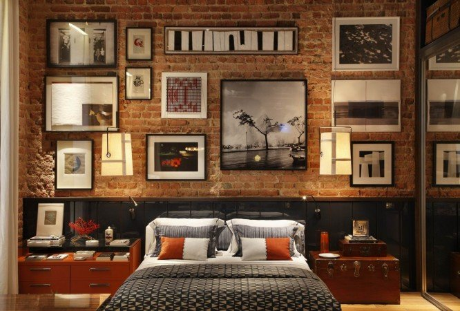 Exposed brick wall serves as gallery in this bedroom