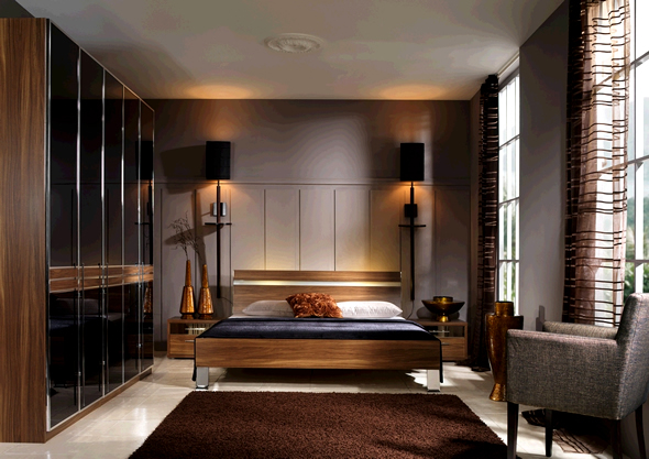 Wood tones of the furniture, the brown area rug and low lighting warm this bedroom