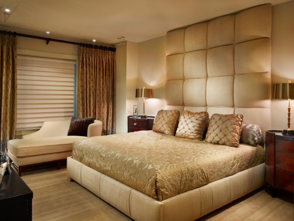A padded headboard and luxurious bedding welcomes in this bedroom