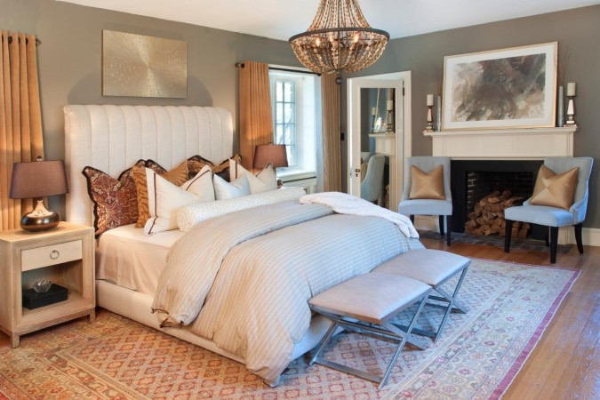 Luxurious bedding and a chandelier enhance this bedroom