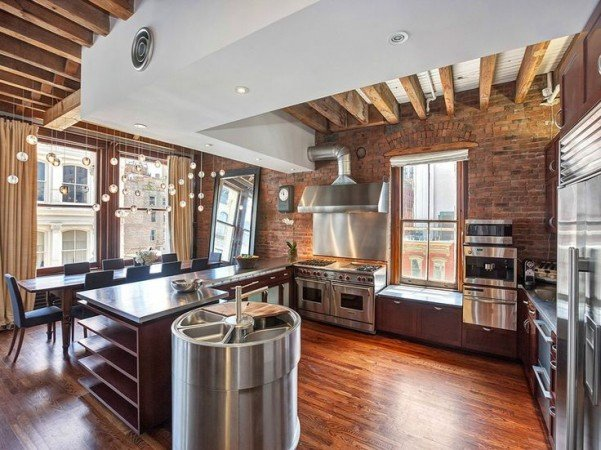 Stainless appliances shine against exposed brick