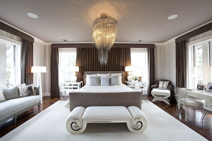 Comfortable benches and a statement chandelier add touches of luxury to this bedroom