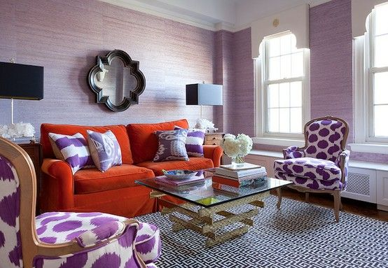 An orange sofa gives interest to this purple room