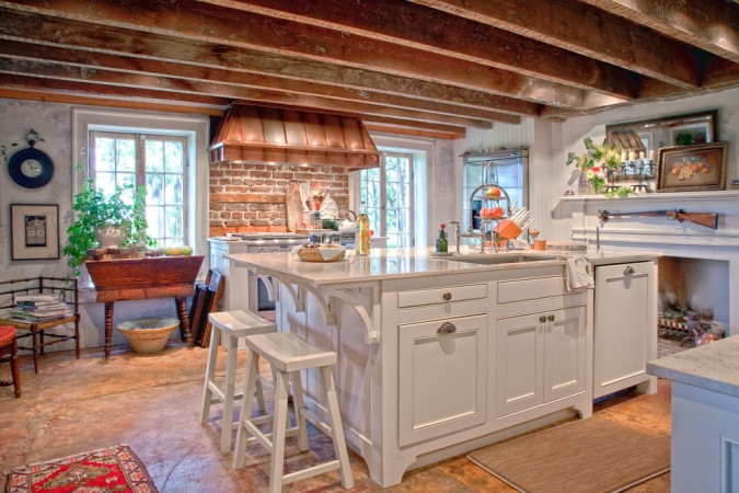 Copper range hood enhances this rustic kitchen