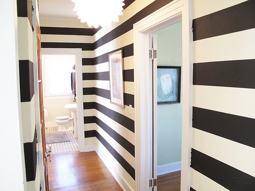 an hallway can seem wider with stiped wall papers