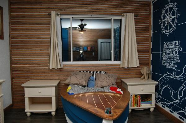 A bedroom with a nautical, fishing theme, featuring boat bed (furnikids).