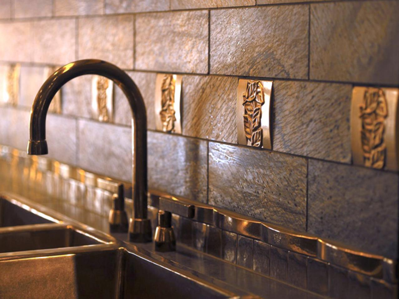 Distressed stone tile with gold leaf-ornament accents (Metallic river-rock back-splash (buildpremier).