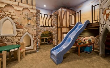 An elaborate tudor-village playroom with slide and lofts (homedit).