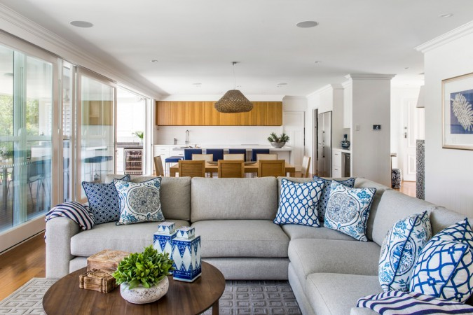 Blue and white patterned pillows add interest and color to this living room