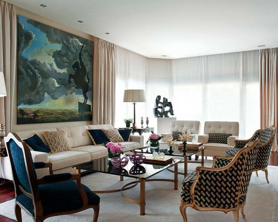 A large painting is the focal point of this stylish living room