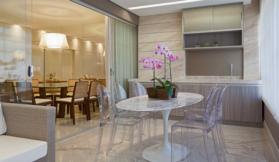 Sleek ghost chairs and glass partition in dining room (homedit)