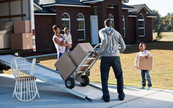 Family moving boxes on to a moving truck