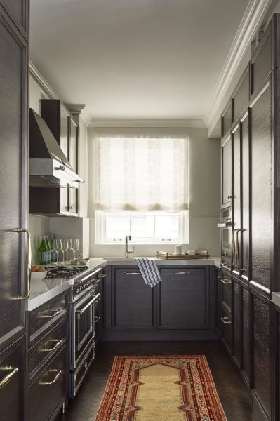 Dark cabinets, a bit shadowy kitchen and a colorful piece of carpet looks great!