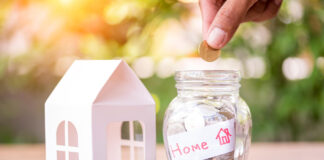 Hand saving money in the glass jar for buying new home