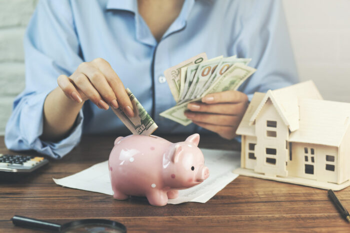 woman hand money and piggy bank with house model on table