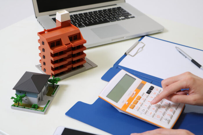 woman uses calculator and house building miniature models on the table
