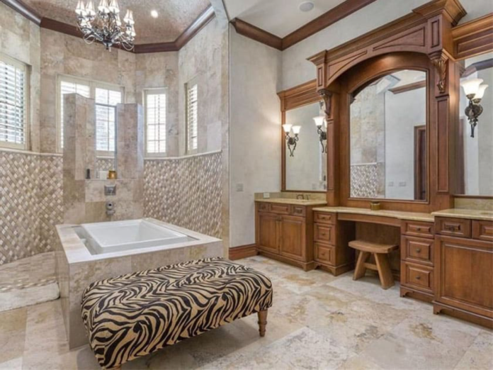 This craftsman bathroom has a unique layout, featuring an open shower are which is directly connected to the square bathtub in the middle