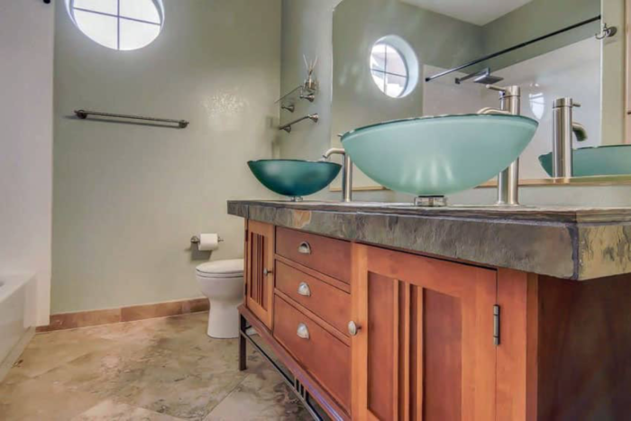 bathroom design combines cool-toned colors with natural warm wood tones for a nice contrast and a balanced look.
