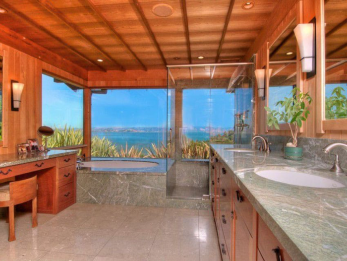 A modern bathroom with a gorgeous view of the ocean through its frame-less picture windows
